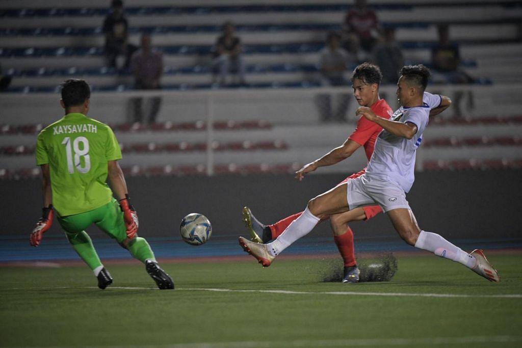Ikhsan (tengah, jersi merah) cuba meledakan gol dalam perlawanan Singapura menentang Laos di Stadium Memorial Rizal malam ini. - Foto BH oleh MARK CHEONG