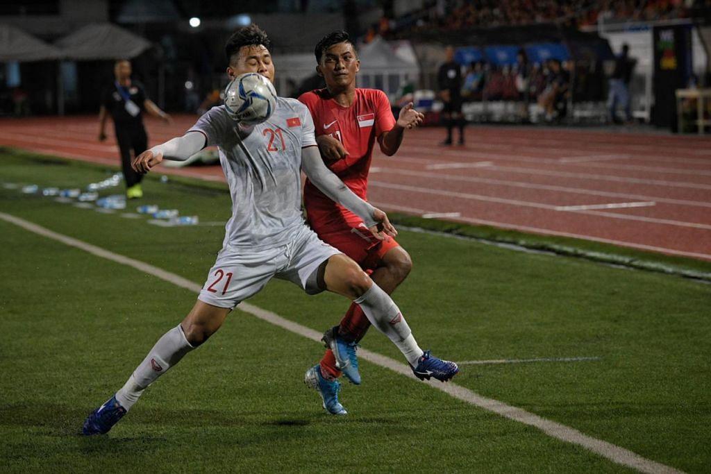 Haiqal Pashia (kanan) dihalang daripada mendapatkan bola oleh pemain Vietnam Nguyen Duc Chien (kiri) di Stadium Memorial Rizal di Manila malam ini (3 Disember). - Foto BH oleh MARK CHEONG