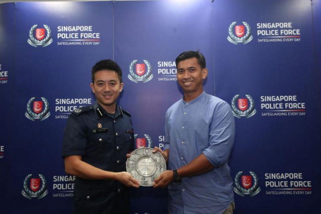 Encik Khairil Anwar Tahir (kanan) menerima Anugerah Semangat Kemasyarakatan Awam yang disampaikan Komander Divisyen Polis Bedok Julius Lim. FOTO: TIMOTHY DAVID