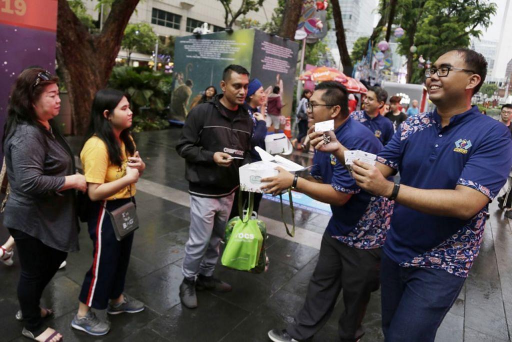 CERMINKAN KEIKHLASAN: Relawan Mesra, MAEC dan daripada beberapa masjid untuk memberi biskut buatan sendiri kepada masyarakat berbangsa lain sempena perayaan Krismas di Orchard Road pada Sabtu lalu. - Foto BH oleh AZMI ATHNI