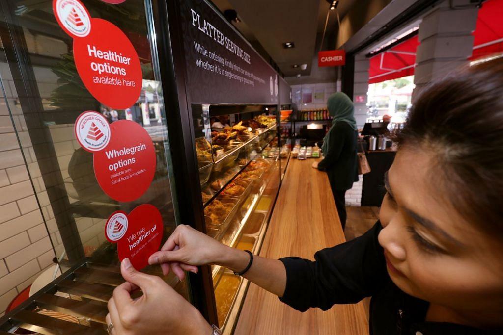 DIJAMIN SIHAT: Seorang kakitangan Rumah Makan Minang meletakkan pelekat simbol pilihan sihat oleh HPB yang menandakan restoran itu juga menyajikan hidangan sihat – Foto fail