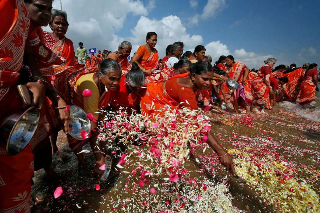 Para wanita menaburkan kelopak bunga ke dalam lautan di Bay of Bengal sebagai memperingati mangsa tsunami yang berlaku 15 tahun lalu di Chennai. FOTO: REUTERS
