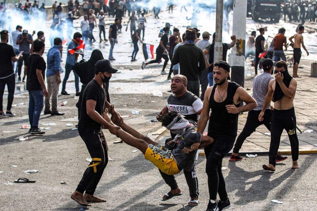 IRAQ TERUS DILANDA KEGANASAN: Foto yang diambil pada 1 Oktober 2019, menunjukkan beberapa penunjuk perasaan membawa rakan yang cedera di tengah pertempuran dengan polis semasa demonstrasi menentang rasuah dan perkhidmatan buruk, di Dataran Tahrir Baghdad. Sekurang-kurangnya 3,000 orang cedera di Baghdad dan Iraq selatan sejak protes antipemerintah meletus pada 1 Oktober. Selepas beberapa dekad konflik bersenjata, Iraq menghadapi pergerakan bantahan akar umbi terbesar dan paling dahsyat, yang mengakibatkan 300 orang terkorban dan 15,000 cedera. – Foto AFP