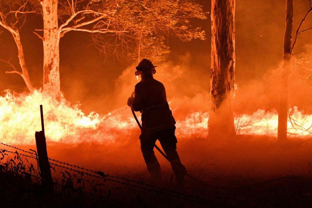 KEBAKARAN HUTAN DI AUSTRALIA: GIGIH PADAM API - Seorang anggota bomba sedang melawan api kelmarin tatkala dunia asyik menyambut ketibaan 2020 dalam usaha untuk menyelamatkan rumah berdekatan daripada hangus dalam kebakaran belukar berdekatan Nowra di New South Wales, Australia. – Foto AFP