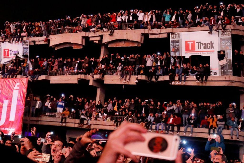 SAMBUTAN DI MESIR: BUKAN DEWAN - Orang ramai berkumpul di bangunan yang belum siap di Waterway, Kahirah, Mesir untuk merakamkan percikan bunga api dengan menggunakan telefon bimbit mereka. – FOTO REUTERS