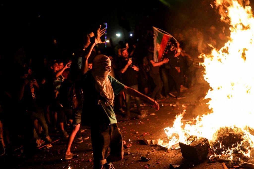 RUSUHAN DI CHILE: API SINAR MALAM - Seorang penunjuk perasaan yang mengenakan topeng beraksi di unggun api sambil menyambut tahun baru di Plaza Italia sewaktu tunjuk perasaan terhadap pemerintah Chile di Santiago. – Foto REUTERS