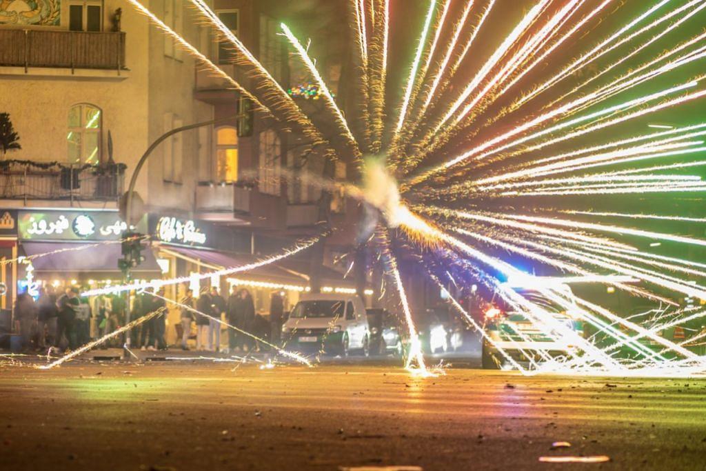 BUNGA API LIAR DI JERMAN:  KEGIATAN BUNGA API LIAR - Bunga api meletup berdekatan kereta polis di daerah Neukoeln di Berlin, Jerman kelmarin. Daerah itu terkenal dengan kegiatan bunga api liar sewaktu malam tahun baru, dengan orang ramai menembak roket ke arah kereta dan bangunan apartmen. – Foto EPA-EFE