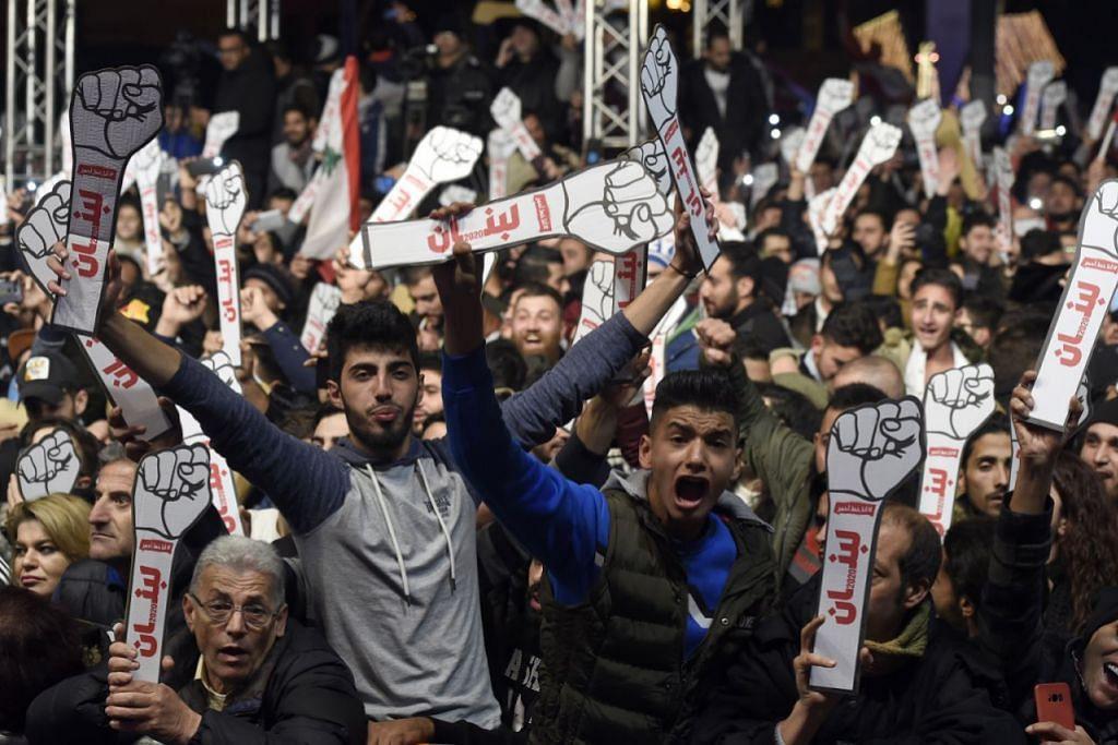 BANTAHAN DI LEBANON: LUAH BANTAHAN MELALUI KERATAN KADBOD - Penunjuk perasaan antipemerintah dan rakyat Lebanon berkumpul sewaktu perayaan malam tahun baru di Martyrs' Square di Beirut, Lebanon, kelmarin. – Foto EPA-EFE