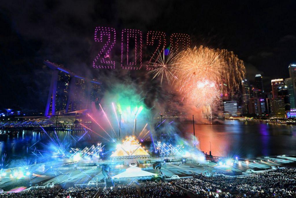 """TERANGI MALAM TAHUN BARU: Dron yang membentuk angka """"2020"""" dengan percikan bunga api daripada muzikal Star Island mewarnai langit malam sedang orang ramai menyambut ketibaan tahun baru di Marina Bay. – Foto BH oleh CHONG JUN LIANG"""