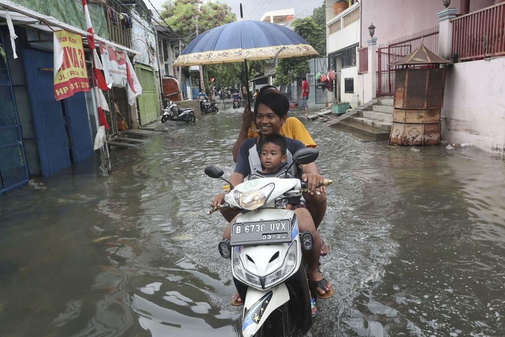 BANJIR BESAR: Penduduk menunggang motosikal melalui jalan yang banjir di Jakarta pada 5 Januari lalu. Banjir yang melanda Jakarta dan bandar-bandar berdekatan telah membunuh sekurang-kurangnya 60 orang, dan menjejas ratusan ribu orang. – Foto: AP