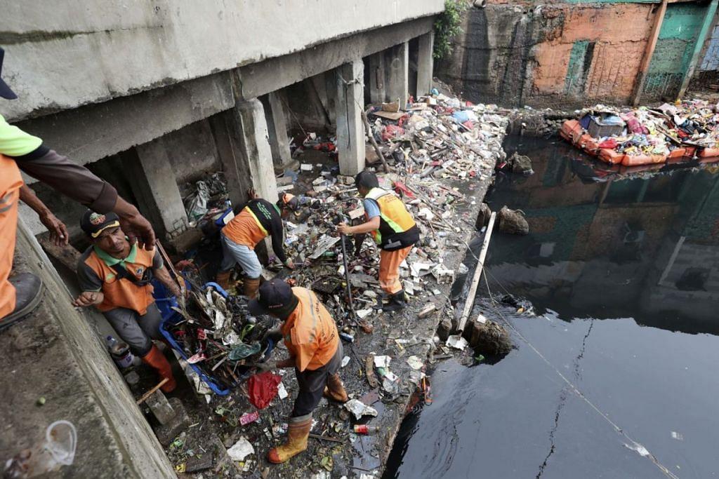 BERSIHKAN SELEPAS BANJIR: Beberapa pekerja mengumpul dan membersihkan sampah yang bertaburan selepas berlaku banjir di Jakarta pada awal tahun baru. – Foto AP