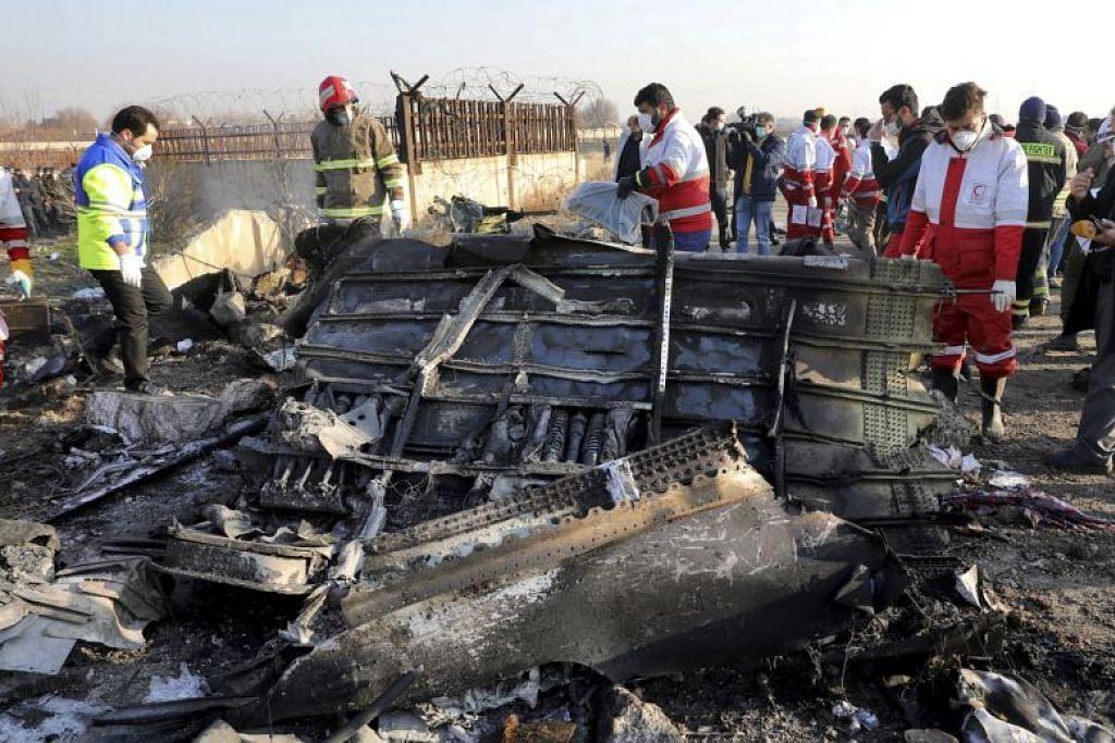 Pekerja penyelamat mencari tempat di mana pesawat Ukraine International Airlines terhempas berhampiran Teheran pada 8 Januari 2020. FOTO: AP