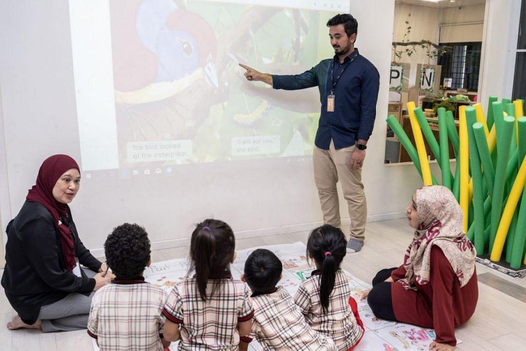 TEKNOLOGI: Encik Thariq sedang menunjukkan cara menggunakan projektor sentuh yang kini sudah mula digunakan dalam bilik darjah di PPIS Bukit Batok. Turut berinteraksi dengan kanak-kanak dan guru adalah Cik Anizah (paling kiri). – Foto BM oleh NUR DIYANA TAHA