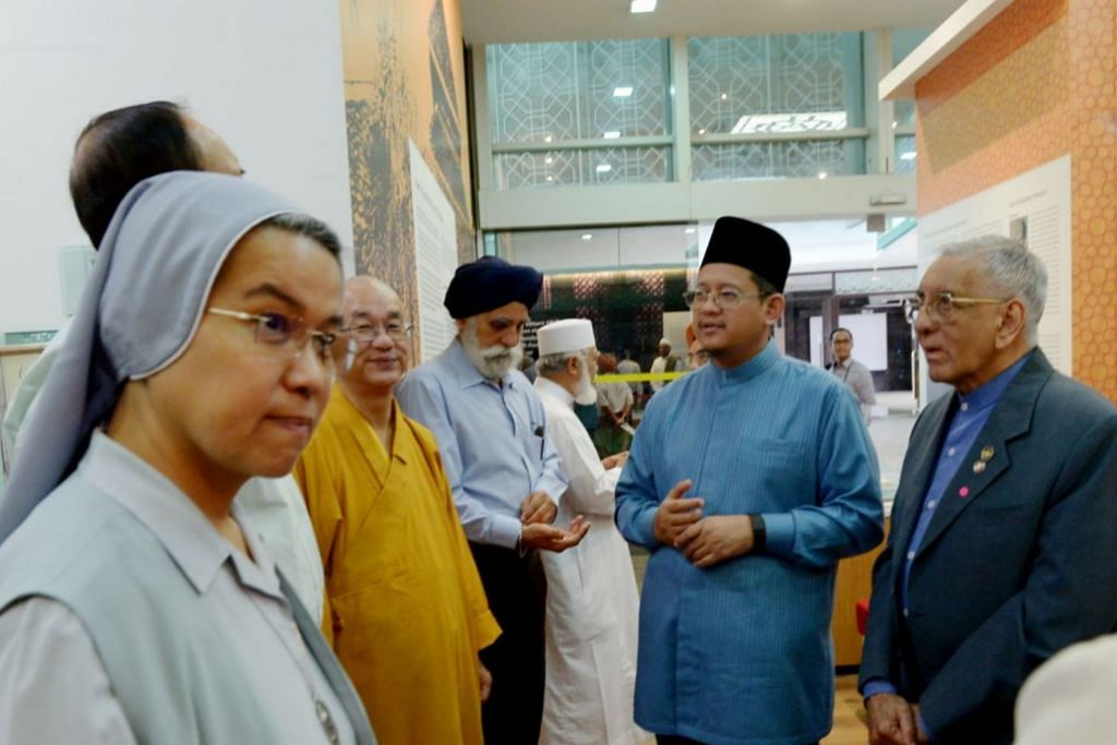 SEKILAS SUMBANGAN MUFTI - MESRA DENGAN PEMIMPIN AGAMA LAIN: Dr Mohamed Fatris Bakaram (tengah), berinteraksi dengan pemimpin agama di majlis teh Aidilfitri di Pusat Harmoni, di Masjid An-Nahdhah. -Foto fail
