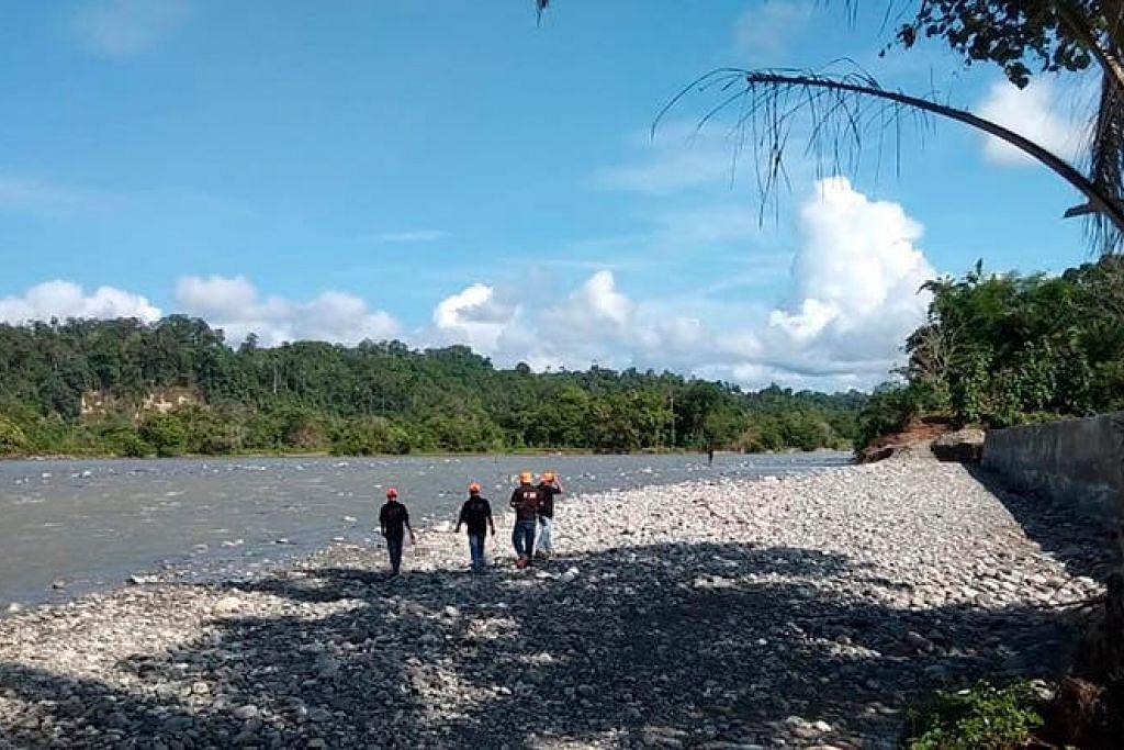 Pegawai penyelamat dan penduduk mencari mangsa setelah jambatan runtuh di Kaur, di wilayah Bengkulu. FOTO: EPA