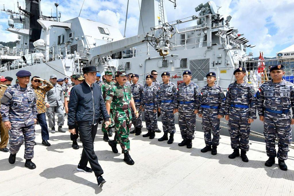 PANTAU KEADAAN: Encik Jokowi (depan) sedang memeriksa sekumpulan tentera semasa beliau melawat kepulauan Natuna baru-baru ini. - Foto AP