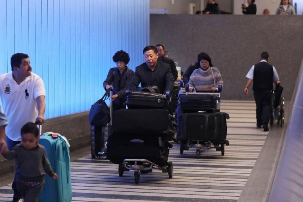 Penumpang pesawat tiba di Lapangan Terbang Tom Bradey di Los Angeles.
