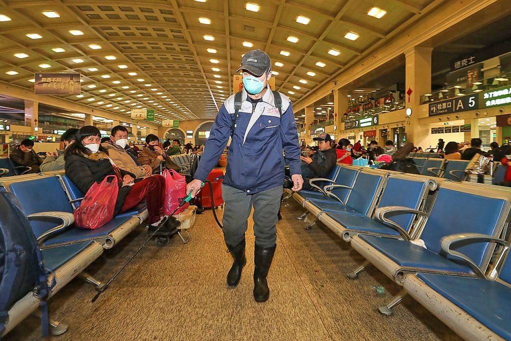 HAPUSKAN KUMAN: Seorang kakitangan melakukan penyahjangkitan di Stesen Kereta Api Hankou di Wuhan semalam. Ratusan juta orang dijangka membuat perjalanan ke serata China bagi cuti Tahun Baru Cina minggu ini. – Foto AFP