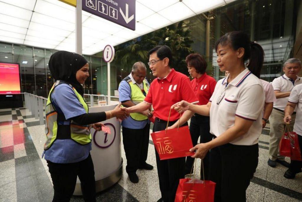 DPM Heng Swee Keat (tengah, baju merah) bersama Presiden NTUC Cik Mary Liew (kanan) memberikan sampul merah kepada pekerja lapangan terbang di Terminal 3 Lapangan Terbang Changi pada 25 Januari ini. - Foto BH oleh TIMOTHY DAVID