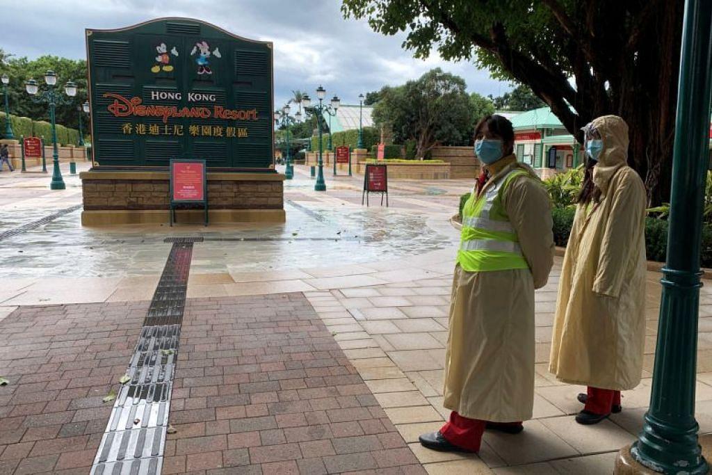 Pekerja di Hong Kong Disneyland berdiri di luar taman tema tersebut yang ditutup dek wabak Wuhan. FOTO: REUTERS