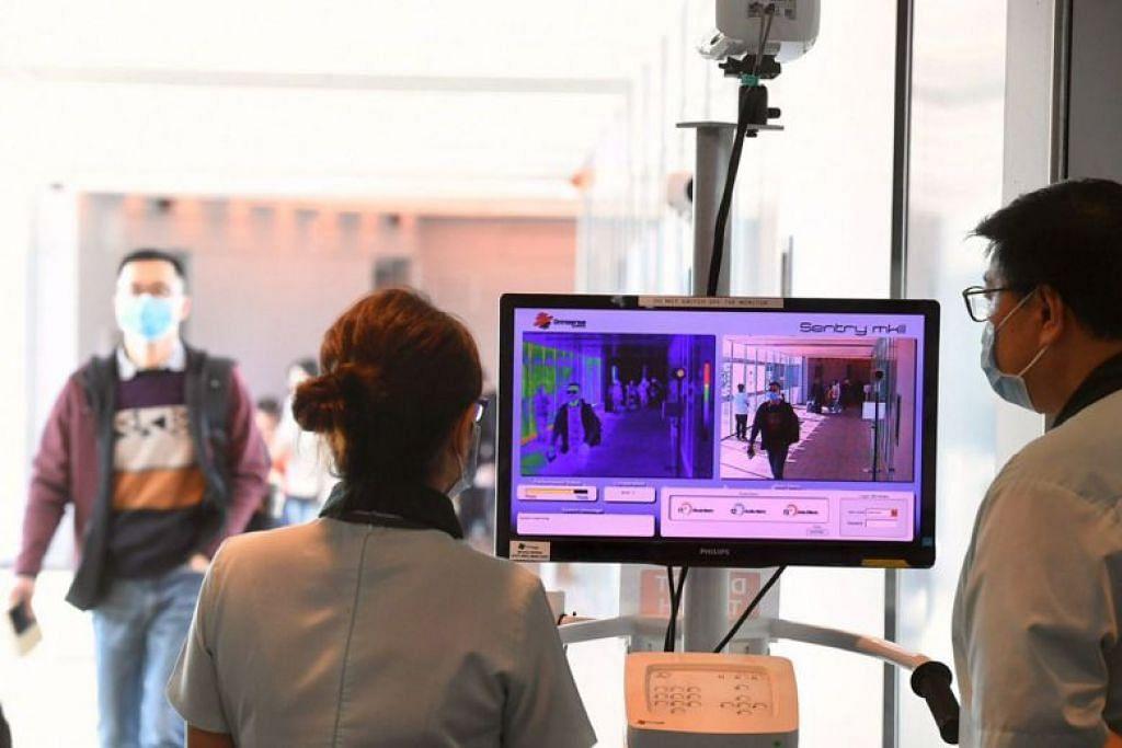 Penumpang yang tiba dari sebuah pesawat dari Hangzhou melalui alat pengimbas suhu badan di Lapangan Terbang Changi.