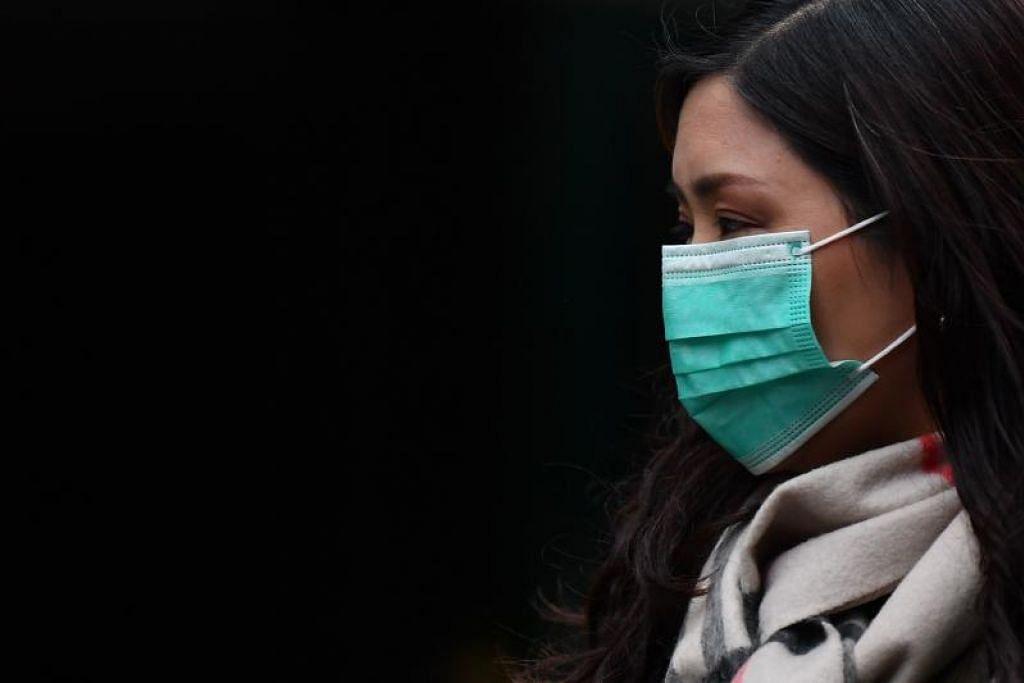 Seorang wanita memakai pelitup muka. FOTO: AFP