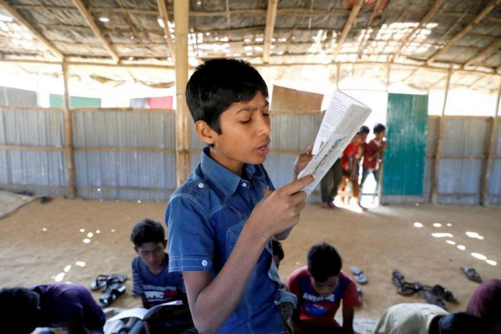 Seorang kanak-kanak membaca buku di sekolah sementara yang dikendalikan guru Rohingya di kem pelarian Kutupalong di Cox's Bazar, Bangladesh pada 7 Februari 2019. FOTO: REUTERS