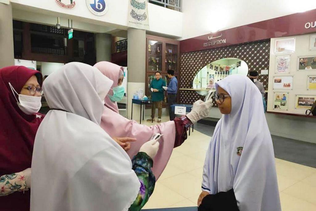AWASI KEADAAN: Kakitangan Madrasah Aljunied Al-Islamiah sedang mengambil suhu badan pelajar secara beramai-ramai sebelum kelas bermula. – Foto FACEBOOK/ MADRASAH ALJUNIED AL-ISLAMIAH