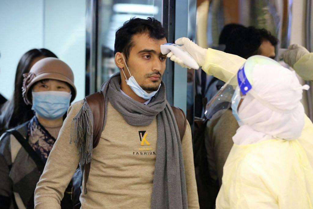 AMBIL LANGKAH BERJAGA-JAGA: Penumpang, yang tiba dari China memakai pelitup untuk menghalang penularan virus wuhan, diperiksa setibanya mereka di Lapangan Terbang Antarabangsa King Khalid di Riyadh, Arab Saudi, kelmarin. – Foto REUTERS