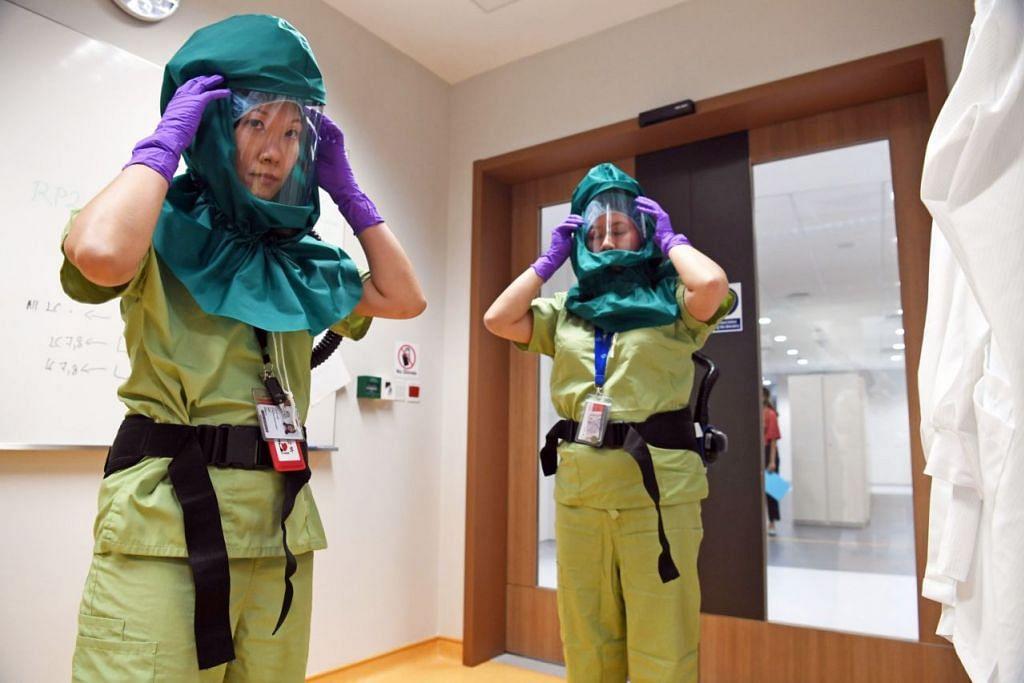 BERUSAHA LINDUNG DARI VIRUS: Teknisyen makmal mengenakan pakaian khas (PAPR) dalam makmal Kesihatan Awam Nasional di Pusat Nasional bagi Penyakit Berjangkit ( NCID). - Foto BH oleh DESMOND FOO