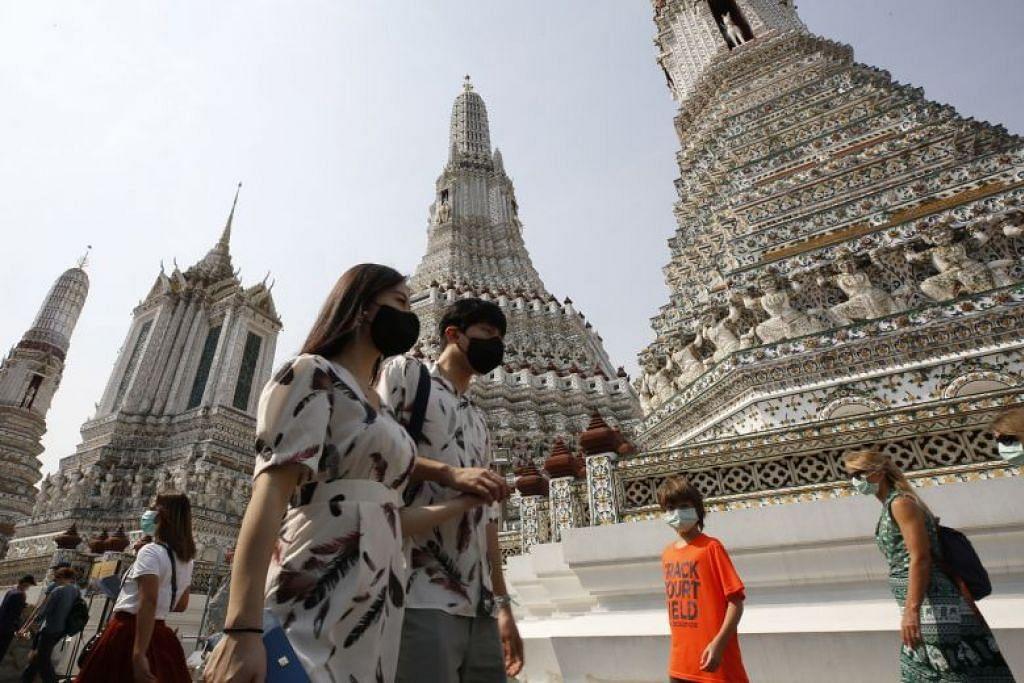 Orang ramai memakai pelitup muka di Wat Arun di Bangkok. FOTO: EPA-FREE