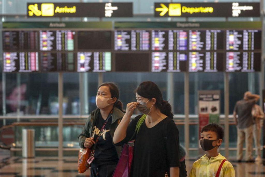 Orang ramai dilihat mengenakan pelitup muka di Lapangan Terbang Changi. FOTO: EPA