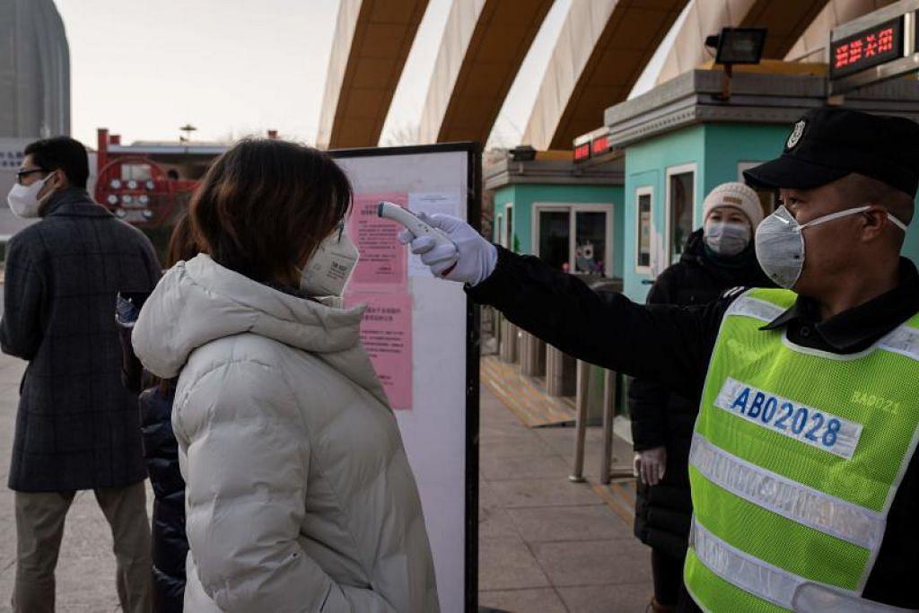 Seorang pegawai keselamatan sedang memeriksa suhu badan seorang pengunjung wanita di pintu masuk sebuah taman di Beijing, sebagai langkah berjaga-jaga di tengah-tengah penularan koronavirus di negara itu.