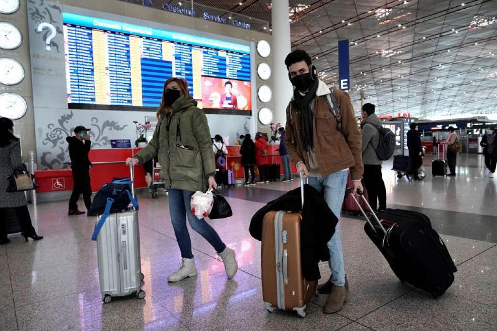 Para pelancong berpelitup muka di lapangan terbang antarabangsa Beijing. Kini pengunjung asing dari China akan tidak dibenarkan masuk ke New Zealand demi menjaga kesejahteraan masyarakat awam negara itu.