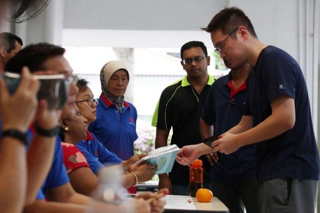 Seorang penduduk sedang mengambil pelitup muka di pusat RC di Blk 47, Telok Blangah Drive, yang diberikan percuma oleh pemerintah dalam usaha membantu warga di tengah-tengah penularan virus korona novel.