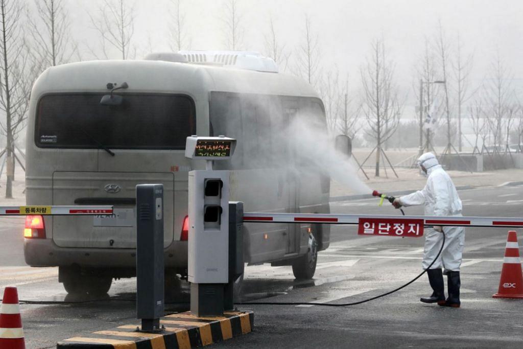 NYAHJANGKIT BAS: Pekerja kuarantin menyahjangkit sebuah bas di Pusat Pembangunan Sumber Manusia Kebangsaan di Jincheon, Korea Selatan semalam. Kemudahan itu digunakan untuk menempatkan warga Korea Selatan yang dibawa pulang dari Wuhan. – Foto EPA-EFE