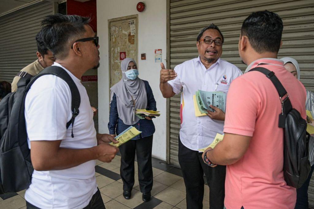 NASIHAT KESIHATAN: Pegawai Jabatan Penerangan Malaysia mengedar nasihat kesihatan kempen cegah jangkitan virus di Kuala Lumpur Jumaat lalu. – Foto AFP