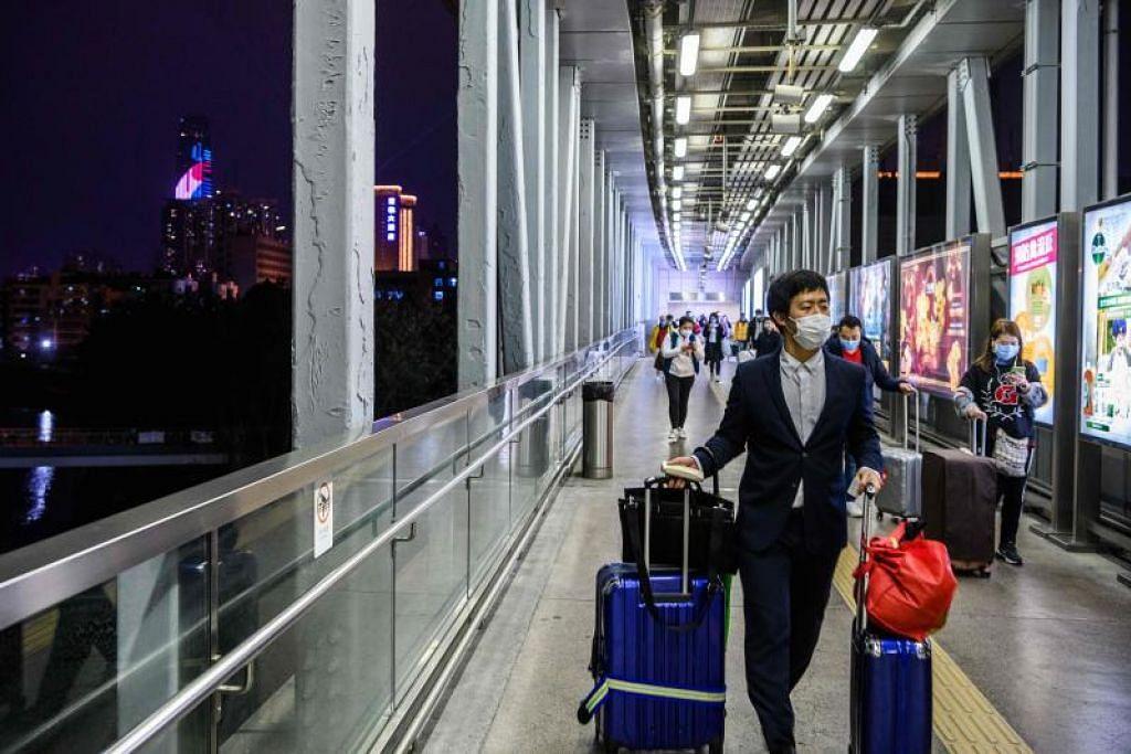KELUAR DARI TANAH BESAR: Penumpang dari bandar Shenzhen di China tiba di stesen MTR Lo Wu di Hong Kong beberapa jam sebelum penutupan sempadan Lo Wu pada Isnin (3 Feb).