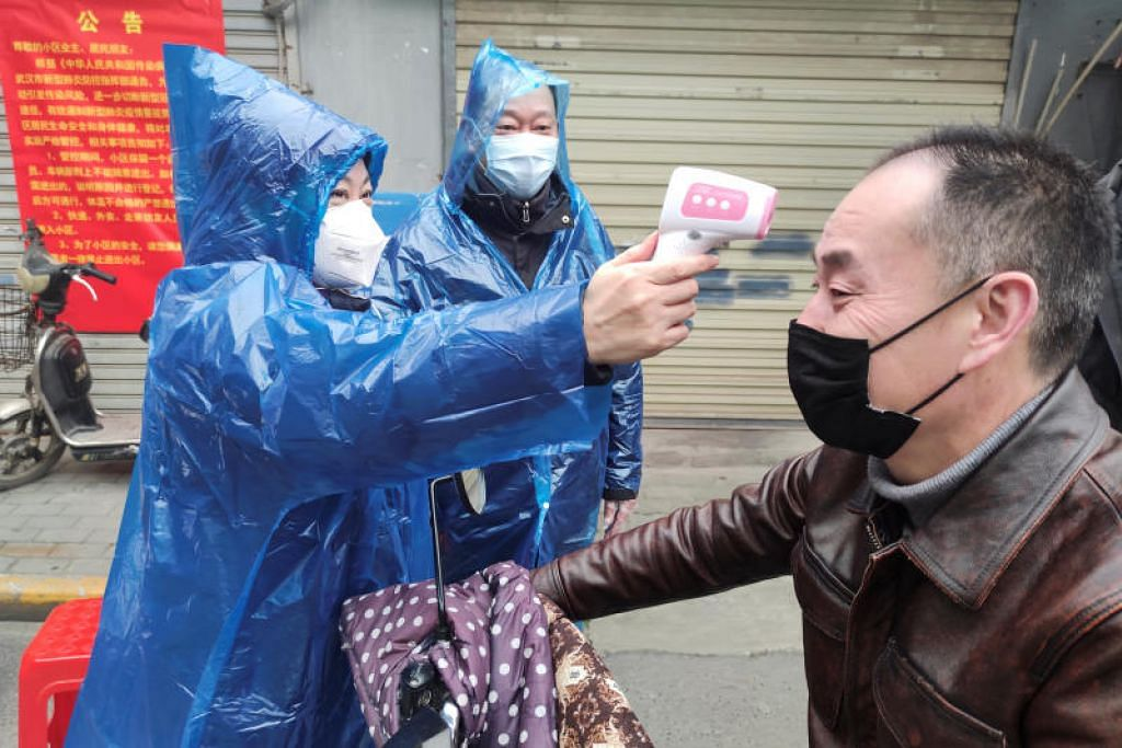 LANGKAH BERJAGA-JAGA: Seorang pekerja mengambil suhu badan seorang lelaki di pintu masuk sebuah kawasan perumahan di Wuhan, Hubei pada 1 Februari lalu.