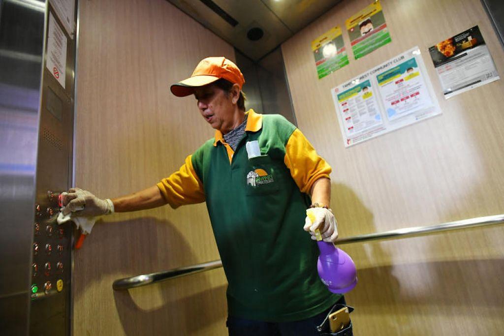 KEBERSIHAN DIPERTINGKAT: Seorang pekerja pembersihan membersihkan butang lif di sebuah blok di Tampines.