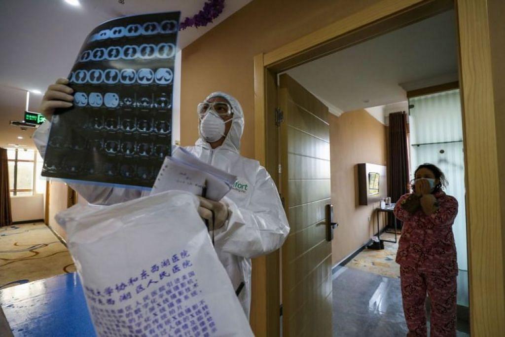 PERIKSA PARU-PARU: Seorang doktor melihat imej CT paru-paru semasa mengunjungi zon kuarantin di Wuhan.