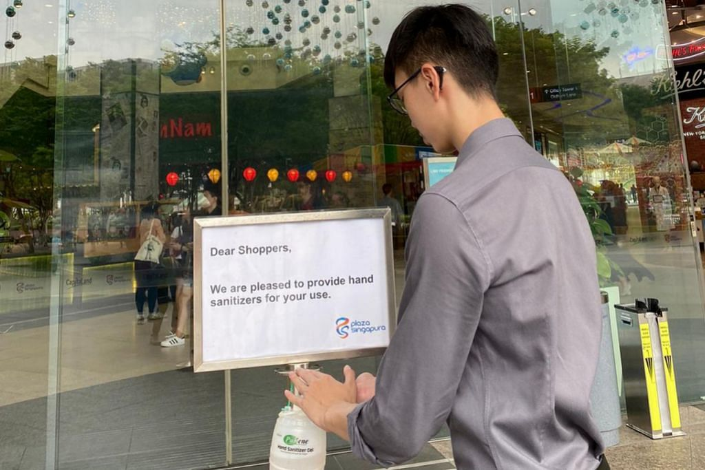 JAGA KEBERSIHAN DIRI: Seorang pengunjung di Plaza Singapura sedang menggunakan sanitiser tangan disedikan di pintu masuk sebelum memasuki pusat belibelah itu. - Foto CAPITALAND