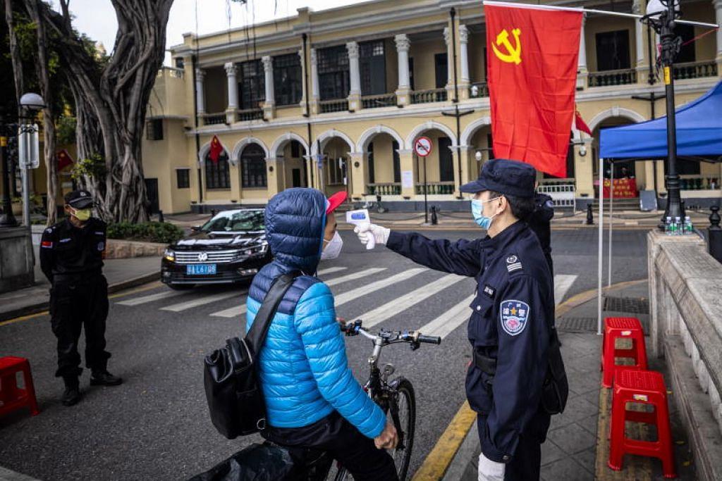 AMBIL SUHU: Pengawal keselamatan memeriksa suhu orang ramai di sekatan jalan raya di Guangzhou, China pada 10 Februari lalu.