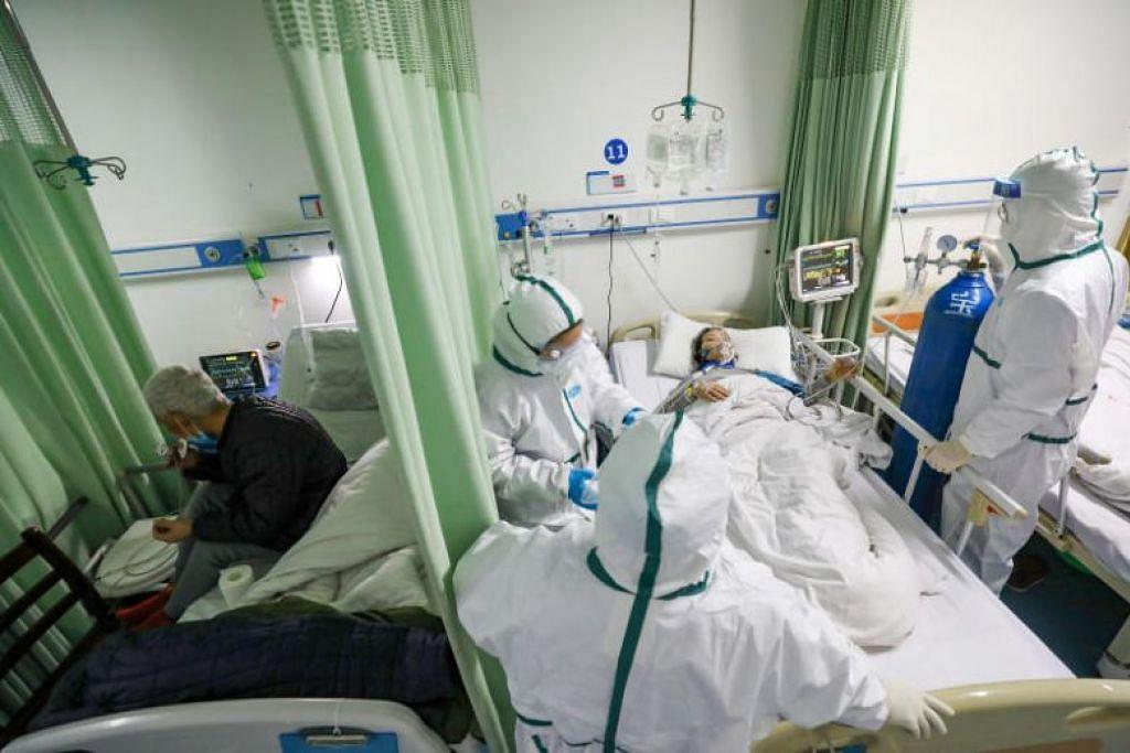 RAWAT PESAKIT: Kakitangan perubatan mengurus seorang pesakit koronavirus di sebuah hospital di Wuhan pada 6 Februari lalu.