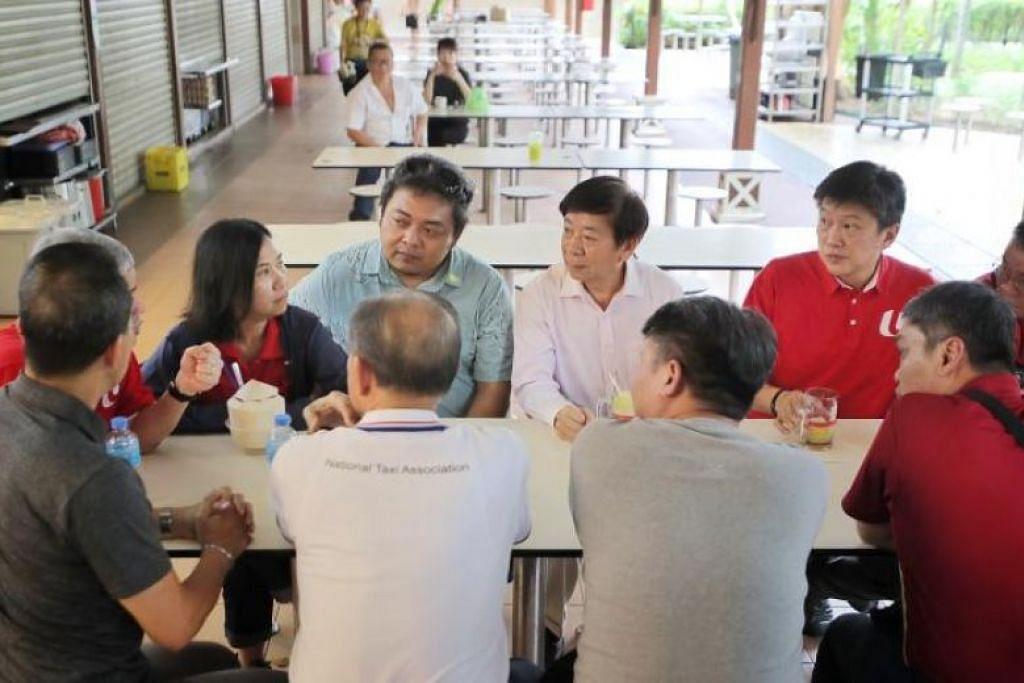 Menteri Pengangkutan Khaw Boon Wan (barisan belakang, tengah) dan setiausaha agung NTUC Ng Chee Meng (menghadap kamera, kanan) bertemu pemandu GrabCare di Pusat Makanan Newton. FOTO: GAVIN FOO