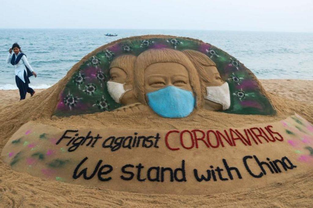 SEMANGAT PERPADUAN: Seorang seniman India menghasilkan arca pasir di pantai Puri di India dengan mesej semangat perpaduan bersama China sedang negara itu memerangi wabak koronavirus.