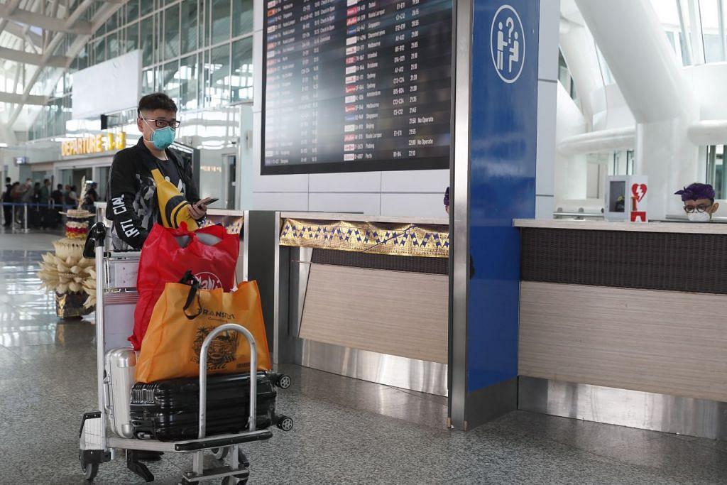 Penumpang pesawat dilihat memakai pelitup di Lapangan Terbang Antarabangsa Ngurah Rai, Bali, Indonesia pada 8 Februari. - Foto: EPA-EFE