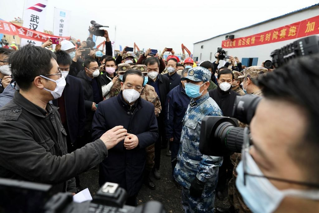 DIGANTI: Bekas ketua Parti Komunis wilayah Hubei, Encik Jiang Chaoliang (tengah) semasa lawatannya ke Hospital Huoshenshan yang baru dibina pada 2 Februari. - Foto: REUTERS