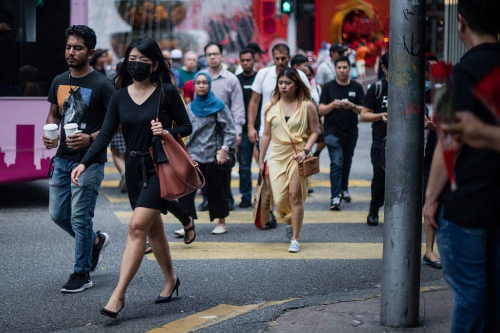 Seorang wanita berkelihatan memakai pelitup di Kuala Lumpur pada 13 Februari. -Foto:AFP.