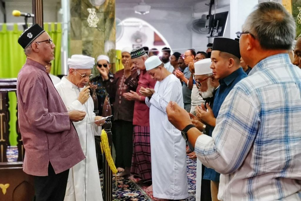 DOA UNTUK KESEJAHTERAAN: Encik Mohamed Abdullah Alhabshee (paling kiri), Imam Masjid Ba'alwie, Syed Hassan Al-Attas (dua dari kiri), dan jemaah masjid mendoakan kesejahteraan Singapura sedang negara ini berdepan dengan wabak koronavirus.